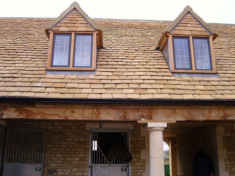 stable building with yellow cotswold stone on roof